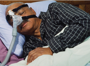 African American man in bed wearing a CPAP mask.