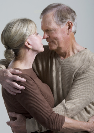 Older man and older woman hugging.