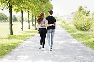 Teen couple lovingly walking arm in arm down a path